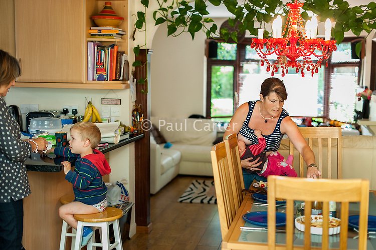 A mother breastfeeds her baby while laying the table and preparing for lunch in the dining room. The grandmother is cleaning the hands of the older child sitting at the breakfast bar.<br /> <br /> 30 August 2012<br /> Hampshire, England, UK