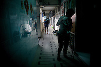 Workers clean a hallway in the Mirador Mansion in the Kowloon district of Hong Kong.  The Mirador Mansion has long been a place for low-budget travelers and immigrants, both legal and illegal, to find a cheap place to stay.