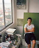 SINGAPORE, Asia, portrait of a young painter Eric Chan sitting on a chair in his studio.
