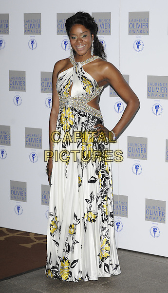ANTONIA OKONMA.The Laurence Olivier Awards 2010, Grosvenor House Hotel, London, England. .21st March 2010.full length white black yellow silver trim maxi dress cut out sides hand on hip.CAP/CAN.©Can Nguyen/Capital Pictures.