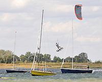 Nils Stephan, Kitesurf-lehrer in der Schladitzer Bucht, zeigt was mit dem Schirm und dem Brett unter den F¸flen moeglich ist. In spektakulaere Manier hebt er hinter den Booten ab, um in Zeitlupe wieder zu landen. Nur fliegen ist schoener. Foto: Alexander Bley .Tel:0163/2494221.AlexBley@gmx.de