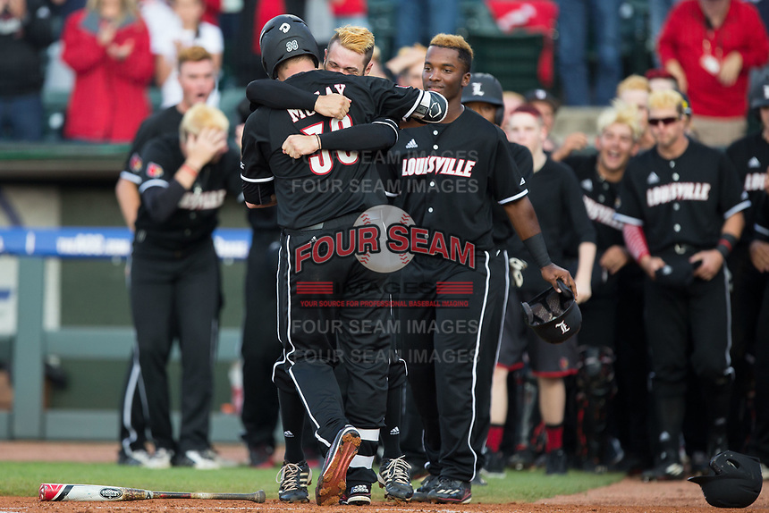 Brendan McKay (38) of the Louisville Cardinals gets a hug from a teammate after hitting a grand slam against the Notre Dame Fighting Irish in Game Eight of the 2017 ACC Baseball Championship at Louisville Slugger Field on May 25, 2017 in Louisville, Kentucky.  The Cardinals defeated the Fighting Irish 10-3.  (Brian Westerholt/Four Seam Images)