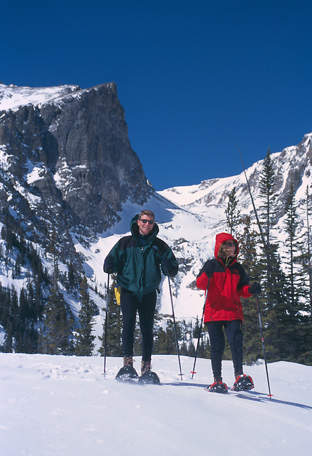 A couple snowshoeing beneath Hallett Peak in Rocky Mountain National Park, Colorado