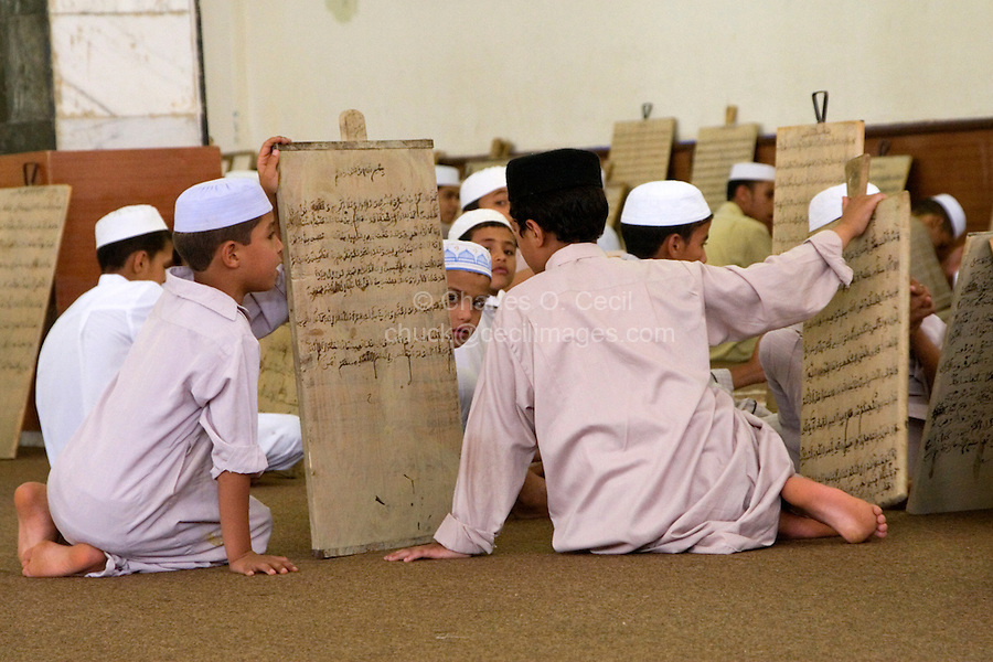 Zliten, Libya. Boys Wait for their Teacher, or Muqri, to Examine their Verses from the Koran Written on their Prayer Boards.  Their course of study eventually leads to the memorization of the Koran.