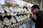 A Palestinian man looks a storefront with imitation jewelry which resembles gold in the West Bank city of Nablus, Aug 19, 2013. With gold prices soaring and high unemployment rate in Palestinian territories, imitation jewelry is in high demand. Photo by Nedal Eshtayah