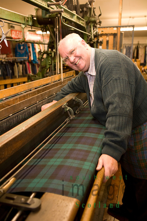 Moffat Woollen Mill weaver George Jackson, who has been weaving since the age of 15, demonstrating how to weave tartan cloth on a Hattersley's Standard loom Moffat Dumfries and Galloway Scotland UK