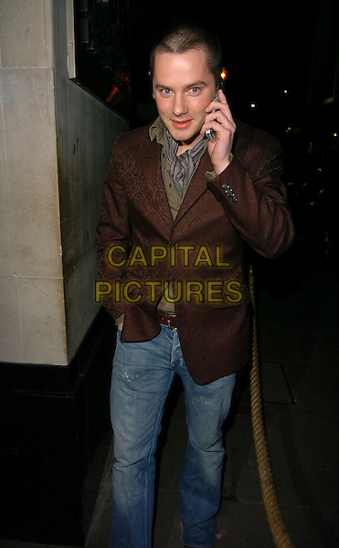 TONY LUNDON - LIBERTY X.The Children in Need Charity Fundraiser, Kensington Roof Gardens, London, UK..March 9th, 2006.Ref: CAN.full length talking on mobile phone jeans denim brown jacket.www.capitalpictures.com.sales@capitalpictures.com.©Capital Pictures