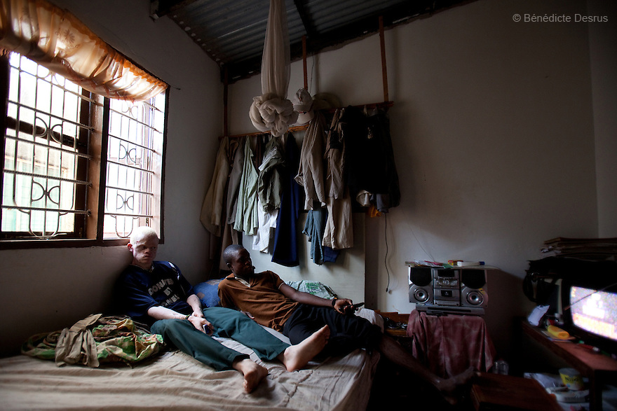 10 june 2010 - Dar Es Salaam, Tanzania - Nixon Samuel Mluge, 22 yrs (L) and his friend (R) watch television on his bedroom. Nixon has badly damaged skin. As well as sun damage, his delicate skin is prone to infections and diseases if not taken care of. Samuel Herman Mluge (51yrs) an albino rights activist in Dar Es Salaam, Tanzania and his wife Teresa January (46 yrs) have five children, all with albinism. Albinism is a recessive gene but when two carriers of the gene have a child it has a one in four chance of getting albinism. Tanzania is believed to have Africa' s largest population of albinos, a genetic condition caused by a lack of melanin in the skin, eyes and hair and has an incidence seven times higher than elsewhere in the world. Over the last three years people with albinism have been threatened by an alarming increase in the criminal trade of Albino body parts. At least 53 albinos have been killed since 2007, some as young as six months old. Many more have been attacked with machetes and their limbs stolen while they are still alive. Witch doctors tell their clients that the body parts will bring them luck in love, life and business. The belief that albino body parts have magical powers has driven thousands of Africa's albinos into hiding, fearful of losing their lives and limbs to unscrupulous dealers who can make up to US$75,000 selling a complete dismembered set. The killings have now spread to neighbouring countries, like Kenya, Uganda and Burundi and an international market for albino body parts has been rumoured to reach as far as West Africa. Photo credit: Benedicte Desrus