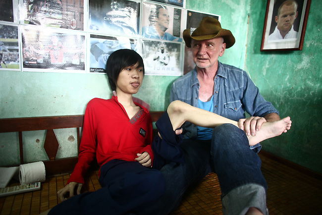 "U.S. war veteran Larry Vetter conducts physical therapy with 18-year-old La Thanh Nghia, near Da Nang, Vietnam. Nghia and his 21-year-old brother Toan are third generation victims of dioxin exposure, the result of the U.S. military's use of Agent Orange and other herbicides during the Vietnam War more than 40 years ago. The two brothers were born healthy, but began to suffer from muscular dystrophy and other problems as they grew older. They are now confined at home, as their bodies and lives literally waste away. Vetter, who served as a Marine Corps infantry officer around Da Nang during the war, met the  the family during his first trip back to Vietnam in 2008 and returned in 2012 to make a finish a documentary film about Agent Orange and the legacy of the war. Vetter says that when he met the family he knew he had to do something, and has helped support them financially ever since. ""They are part of my life now,"" he says. ""And I'm part of theirs."" The Vietnam Red Cross estimates that 3 million people suffer illnesses from dioxin exposure, including at least 150,000 children born with severe birth defects since the end of the war. The U.S. government last year began paying for the removal of dioxin from the heavily contaminated Da Nang airport, which served as a major U.S. base, but U.S. officials still deny that dioxin is to blame for widespread public health problems in Vietnam, and the U.S. government has yet to provide any aid money specifically to help the country's Agent Orange victims. Jan. 5, 2013."