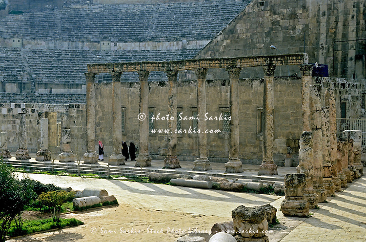 People walking by the ruins of the Roman theatre, Amman, Jordan.