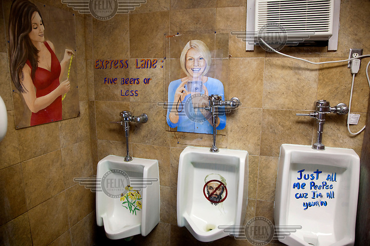 A picture of Osama Bin Laden painted on a men's urinal in a bar in Florida, along with other images painted onto the wall....
