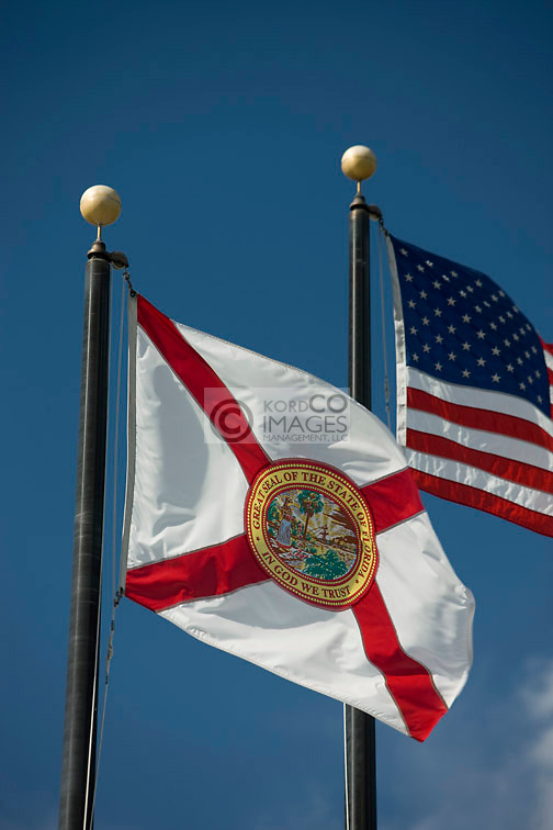 FLORIDA STATE FLAG UNITED STATES FLAG FLYING ON FLAGPOLES ON BLUE SKY BACKGROUND