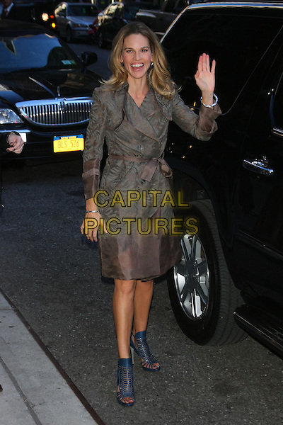 HILARY SWANK.Hilary Swank at the Ed Sullivan Theater for an appearance on the 'Late Show with David Letterman', New York, NY, USA..October 13th, 2010.full length beige grey gray print coat jacket blue strappy sandals hand waving palm.CAP/LNC/TOM.©LNC/Capital Pictures.