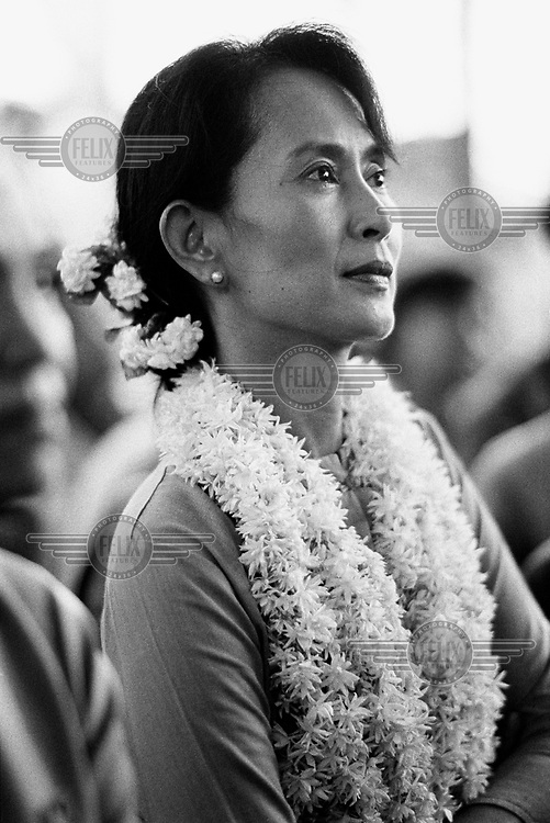 A portrait of Daw Aung San Suu Kyi, the Nobel Peace Prize Laureate and General Secretary of the National League for Democracy (NLD), sitting among supporters and watching performances during the celebrations for Burmese New Year in the grounds of her family home.