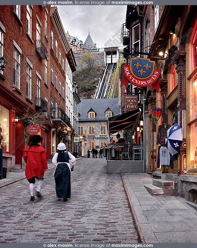 Two people in medieval costumes walking up the Rue Sous Le Fort street in old Quebec City with funicular in the background. Souvenirs du Lys, Sous le Fort, La Chasse-Galerie boutique and other shops and restaurants. Quebec, Canada. Rue Sous-Le-Fort, Ville de Québec.
