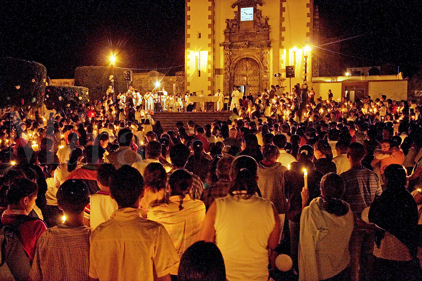 Devout ;CATHOLICS light candles during EASTER MASS at SAN ANTONIO CHURCH - SAN MIGUEL DE ALLENDE, MEXICO .