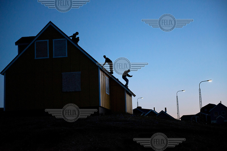 Youths play at night on an abandoned house in Narsaq...
