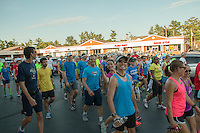 Runners walk through the parking lot of the Fleet Feet Des Peres store before hitting the street for the Run with Meb Keflezghi run in St. Louis County,  Wednesday, September 3, 2014.