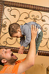 Young father with 16 month old toddler son physical play