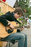 USA, Alaska, Talkeetna, a young man Ian Merkley plays the guitar on the street in town