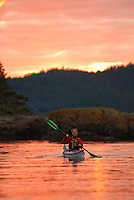 Smiling female sea kayaker paddling in the colorful orange light of sunset, Stuart Island, San Juan Islands Washington