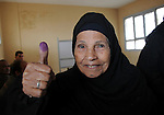 An Egyptian woman shows her ink-stained finger after she voted at a polling station in Giza district near Cairo on December 21, 2011 in the run-off of the second round of legislative election marred by deadly clashes between protesters and security forces. Photo by Ahmed Asad