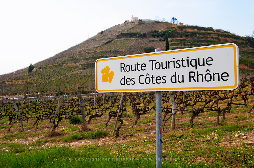 A road sign saying Route Touristique des Cotes du Rhone, Touristic roads in the CdR, in the background the Hermitage hill with the Maison Blanche house and vineyard. The Hermitage vineyards on the hill behind the city Tain-l'Hermitage, on the steep sloping hill, stone terraced. Sometimes spelled Ermitage. Tain l'Hermitage, Drome, Drôme, France, Europe