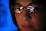 Proteomics is the study of the structure and function of proteins in an organism. The scientist shows reflections of protein molecular models on her eyeglasses.