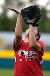 A Little League softball player prepares to catch a pop fly.