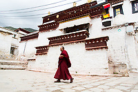 A monk walks through Ganden monastery in Tibet. The monastery is one of the most important in the region and sits on top of a mountain near Lhasa at an altitude over approximately 4,300m.