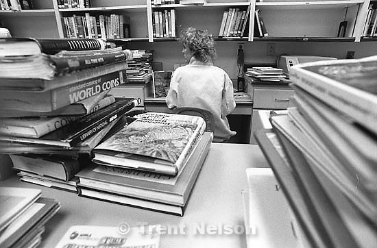 Librarian surrounded by returned books for a story on the Provo Library being overcrowded.<br />