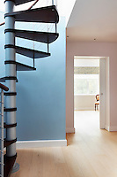 A minimalist hallway with a wooden floor and one blue and one pink painted wall. An open sliding door leads to a bedroom beyoond. A spiral staircasae leads up to a converted attic space.