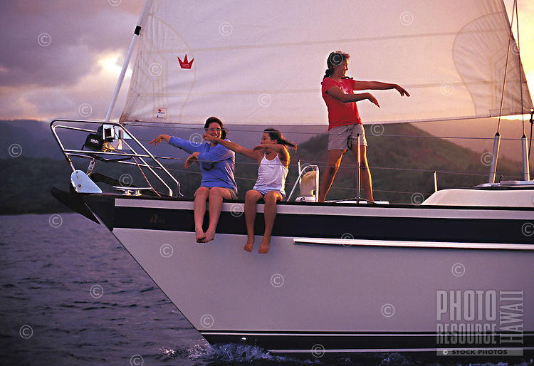 Woman and girls dancing hula as they sail into Hanalei Bay at sunset, North Shore, Kauai, Hawaii