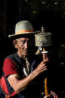 A traditional Tibetan with his prayer wheel in the streets of Lhasa early morning