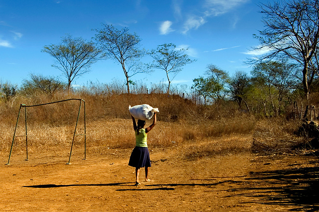 Young girl balances a load of laundry on her head as she heads home in San Jacinto, Nicaragua.