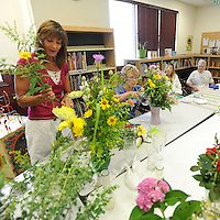 NWA Democrat-Gazette/ANDY SHUPE<br /> Marcey Abrecht (left) of Farmington demonstrates Thursday, Aug. 6, 2015, flower-arrangement techniques for members of the newly established Farmington Garden Club at the Farmington Public Library. The club was established with the goal of providing beautification projects around town in addition to the education and enjoyment of its members.