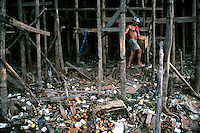 A man walks among the legs of a produce and meat market at the Amazon port city of Manaus. Due to massive flood stages, most structures in the Amazon either float or stand on stilts. The space below the floor of the local market serves as a garbage dump.