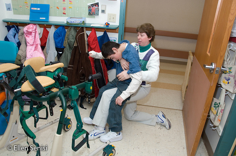 MR / Albany, NY.Langan School at Center for Disability Services .Ungraded private school which serves individuals with multiple disabilities.Physical therapist takes child out of gait trainer. Boy: 11, cerebral palsy, expressive and receptive language delays.MR: Bro12; Pie3.© Ellen B. Senisi