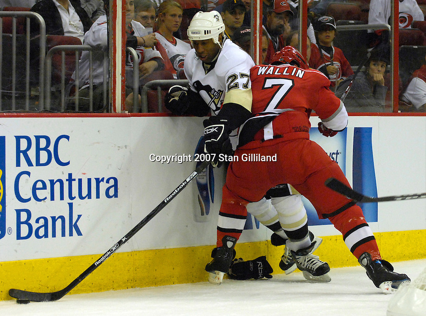 Pittsburgh Penguins' Georges Laraque and the Carolina Hurricanes' Niclas Wallin battle for a puck during their game Friday, Oct. 5, 2007 in Raleigh, N.C. The Hurricanes won 4-1.