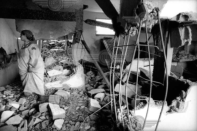 A woman looks through the ruins of her home in the Bureij camp after it was destroyed by the Israeli Defence Force (IDF).