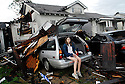 Ashley Gullo, 17, sits outside of her home damaged by an early morning tornado in New Orleans, Tuesday, Feb. 13, 2007. She was asleep in the trailer with her family when the tornado stuck. (Cheryl Gerber for New York Times)
