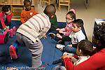 Education preschool 4 year olds circle time web with string activity horizontal female teacher assisting