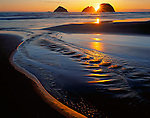 Tillamook County, OR   <br /> Setting sun silhouetting Three Arch Rocks (National Wildlife Refuge) with stream reflections on the receding tide