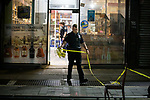 An NYPD officer removes police take after an investigation into a double shooting at a liquor store at 1563A Fulton Street on July 16, 2020 in the Brooklyn borough of New York City.  Photograph by Michael Nagle