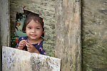An indigenous girl peers through a hole in a fence in the Nacoes Indigenas neighborhood in Manaus, Brazil. The neighborhood is home to members of more than a dozen indigenous groups, many of whose members have migrated to the city in recent years from their homes in the Amazon forest.
