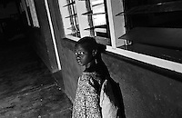 A young girl on the veranda at St. MaryÕs Hospital. The hospital is one of the few places children, known as Night Commuters, can find protection every  night to avoid being abducted by the Lords Resistance Army (LRA) in Northern Uganda. The LRA is primarily made up of abducted youth. Night Commuters find much more than safety in the compounds, they also find friendships, activity and fellowship. Tens of thousands of children, on average, make this exodus every evening. The war in Northern Uganda has been transpiring for two decades. Lachor, Gulu District, Uganda, Africa. July 2004 © Stephen Blake Farrington.