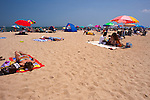 Solitary sunbathers lie scattered among family groups, umbrellas, and shelters on a sunny summer beach day at Rehoboth Beach, Delaware, USA.