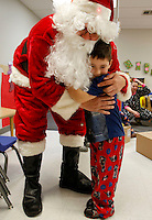 NWA Media/DAVID GOTTSCHALK - 12/19/14 - Nate Tinsley receives a hug from Santa Claus in the three to five year old class of Marty Fink at Bentonville Public Schools Childcare Enrichment Services Building Bridges Friday December 19, 2014 in Bentonville.  Sponsored by United Way Gift of Kindness Warehouse, the children at the school read holiday stories, enjoyed hot chocolate and received a visit from Santa Claus who delivered gifts.