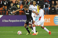 Washington, D.C.- March 29, 2014. Nick DeLeon (14) of D.C. United shields the ball against Daigo Kobayashi (16) of the New England Revolution.  D.C. United defeated the New England Revolution 2-0 during a Major League Soccer Match for the 2014 season at RFK Stadium.