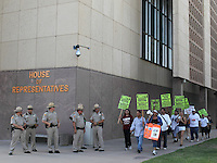sb1070  7/28/10-A group of anti-SB1070 activists walk past a group of law enforcement officers outside the Arizona House of Representatives Wednesday afternoon. (Pat Shannahan/ The Arizona Republic)